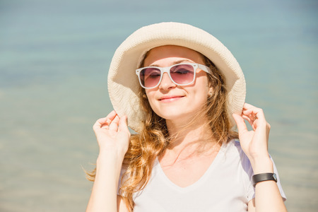 releaxed: Bright portrait of attractive young woman in sunglasses on the beach having sunbath