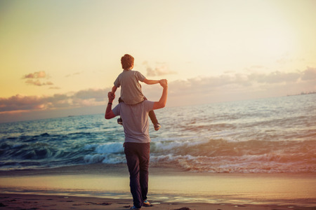 lifestyle outdoors: Happy father and son having quality family time on the beach on sunset on summer holidays. Lifestyle, vacation, happiness, joy concept