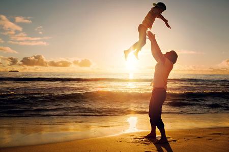 padres: Padre e hijo feliz que se divierten juntos en la puesta del sol del oc�ano en las vacaciones de verano Foto de archivo