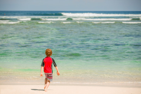 bali beach: Cute 7 years old boy in red rushwest swimming suit and shorts having fun on tropical Bali beach with white sand and green ocean Stock Photo