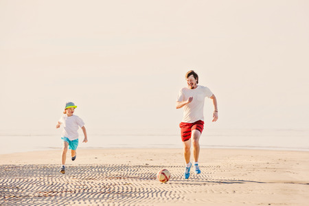 football play: Happy father and son play soccer or football on the beach having great family time on summer holidays. Lifestyle, vacation, happiness, joy concept