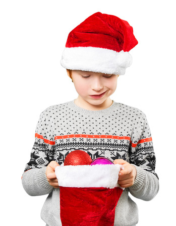 skeptic: Portrait of a boy in red christmas hat with skeptic facial expression looking at the christmas balls and toys in his hands, isolated on white. Stock Photo