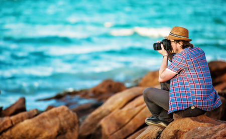 Young photographer taking photos at the beach of the beautiful seascape in sunet light