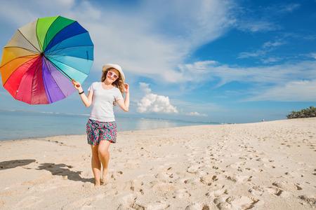 vida sana: Chica joven alegre con el paraguas del arco iris que se divierten en un día soleado en la playa con un hermoso mar y el cielo azul en background.Travel, días de fiesta, vacaciones, estilo de vida saludable concepto