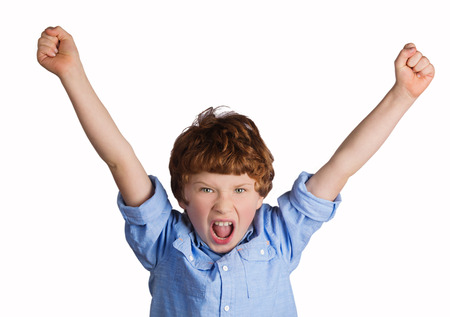 winning mood: Handsome caucasian boy celebrating victory or success screaming and throwing hands in the air. Isolated on white background Stock Photo