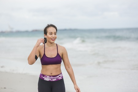 Runner woman finishing work out on beach smiling happy. Beautiful vivacious woman jogging on the beach with cloudy weather Stock Photo