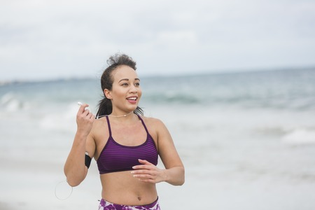 vivacious: Runner woman finishing work out on beach smiling happy. Beautiful vivacious woman jogging on the beach with cloudy weather Stock Photo