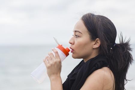 mujer deportista: Brunette joven atractivo que el enfriamiento y el agua potable de una botella después de hacer ejercicio en la playa