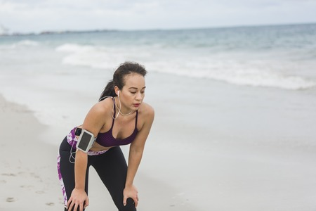 vivacious: Runner woman resting after long run on the beach. Beautiful vivacious woman jogging on the beach with cloudy weather