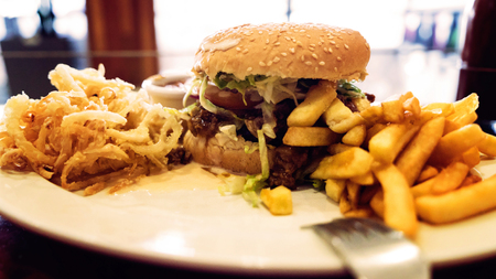onion rings: Unhealthy meal with mexican nacho chips, beef burger, loaded with cheese, fries, onion rings