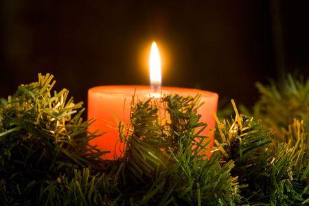 red candle burning on black background