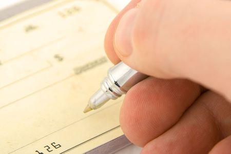 endorsing: signing check close up with shallow depth of field Stock Photo
