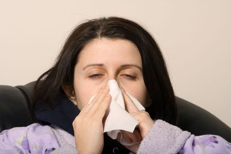 sniffles: woman with a cold blowing her nose with a tissue