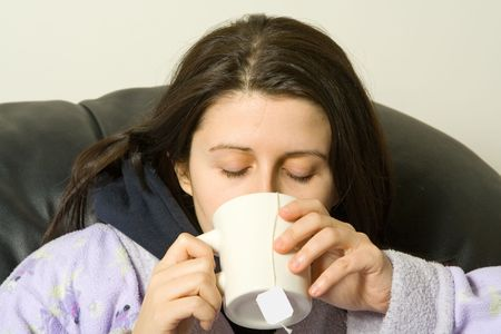 woman with a cold drinking a hot tea