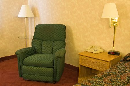 hotel room with recliner nightstand and bed photo