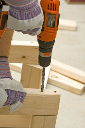 man drilling a hole into wood with cordless drill