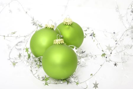 green ornaments with silver stars isolated against white background
