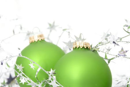 two green ornaments with silver stars isolated against white background