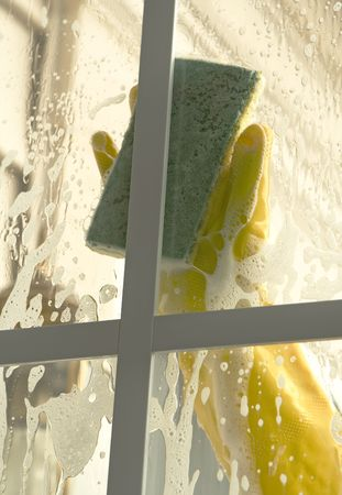 woman cleaning window with a sponge
