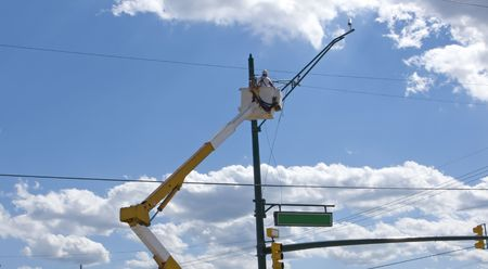 outage: worker changing light fixture on a post Stock Photo