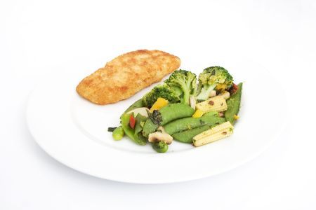 breaded piece of fish with vegetables on a plate