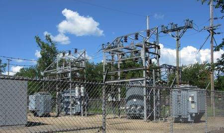 fenced electical power substation with clouds background