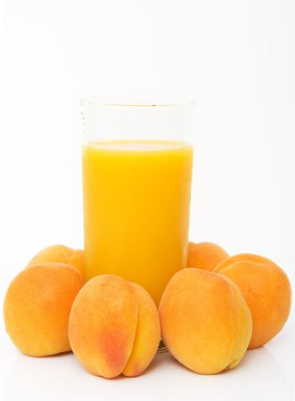 studio shot of fresh apricots with glass of juice isolated against white background Stock Photo