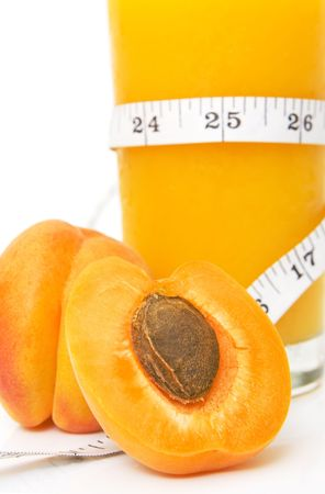 glass of tasty juice with measuring tape and apricots isolated against white background