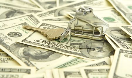 house shaped keychain with money background Stok Fotoğraf