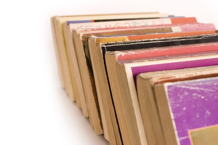tatty: Row of colorful old paperback books on white background with space for copy