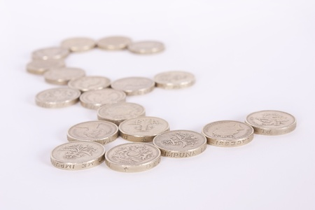 gbp: Pound symbol made from gold pound coins on a white background with shallow depth of field.