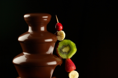melted chocolate: Fruits in chocolate fountain Stock Photo