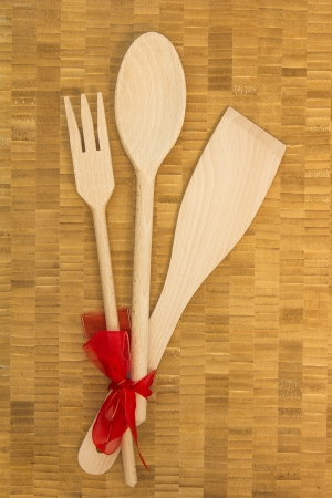 Wooden Kitchen Utensils with Red Ribbon on Wooden Background photo