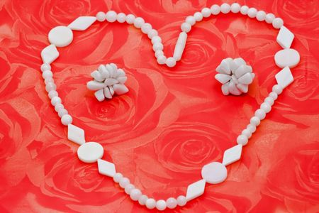 Heart shapted white bone necklace and earrings on roses background photo