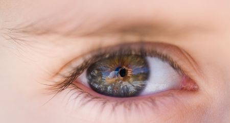 Close-up of a boy's eye reflecting the photographer and the landscape Stock Photo - 2366018