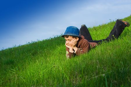 Beautiful kid relaxing in grass under blue sky