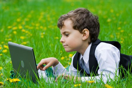 seven years: Seven years old businessman with his laptop on a meadow Stock Photo