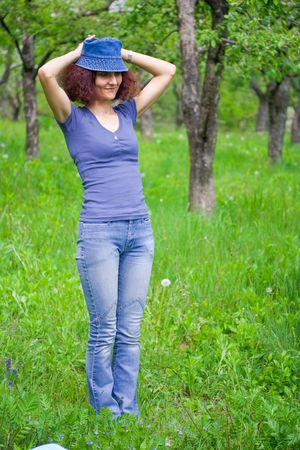 Beautiful redhead woman with cap in an orchard photo