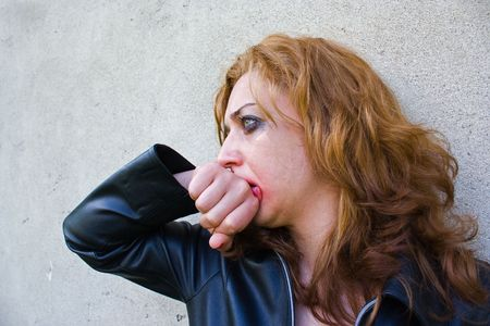 Portrait of an abused blond woman near a wall photo