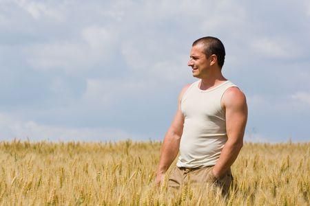 hombre fuerte: Joven hombre fuerte con una camiseta en un campo de trigo