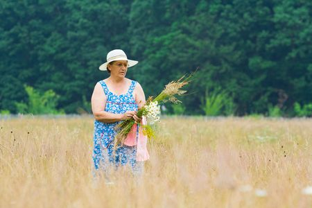 Portrait of an old woman with hat picking flowers near a forest Stock Photo - 3250734