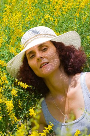 portrait of a beautiful lady with hat in a flower field photo