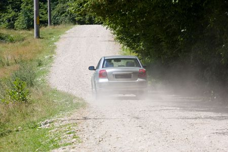 Silver car at high speed on a country-side road without pavement photo