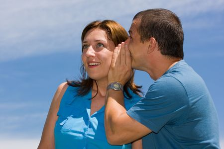 Young couple sharing secrets under blue sky Stock Photo - 3281685