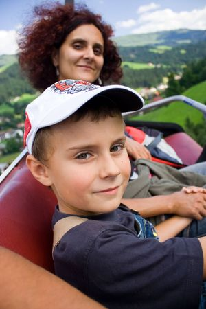 Mother and son in a cableway chair above the mountain photo