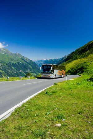Bus with tourists driving uphill in Alps Stock Photo - 3365895