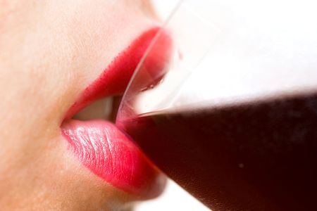 Closeup of beautiful female lips drinking wine from a glass with dewdrops on it Stock Photo