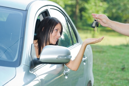 Beautiful teen-ager receiving car keys photo