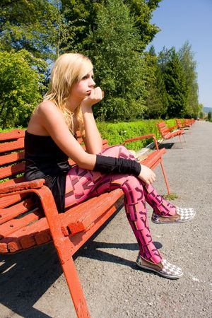 Portrait of a beautiful blonde woman sitting on a bench in park photo