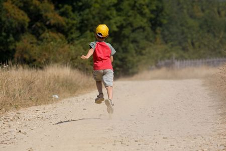 seven year old: Seven year old kid running on a dusty road in the countryside Stock Photo
